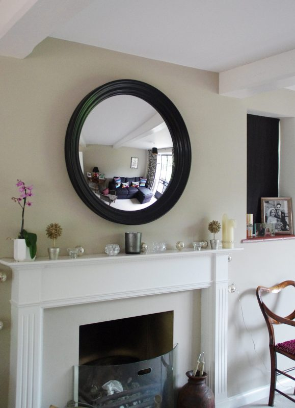 Large Roma convex mirror in waxed black hanging above a fireplace in a living room image