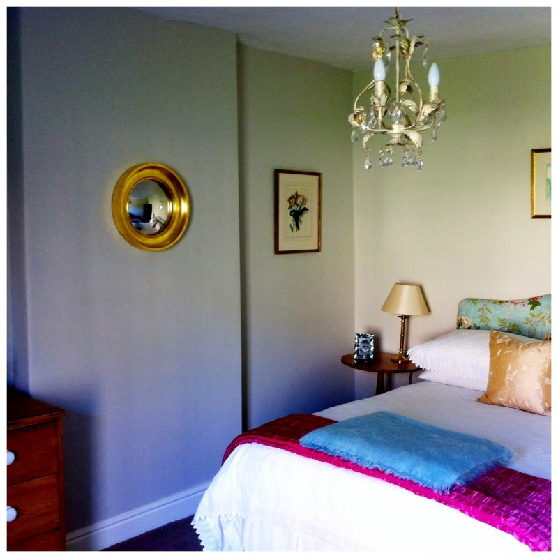 Small Cavetto decorative convex mirror in gold leaf finish hanging in a bedroom in-situ image