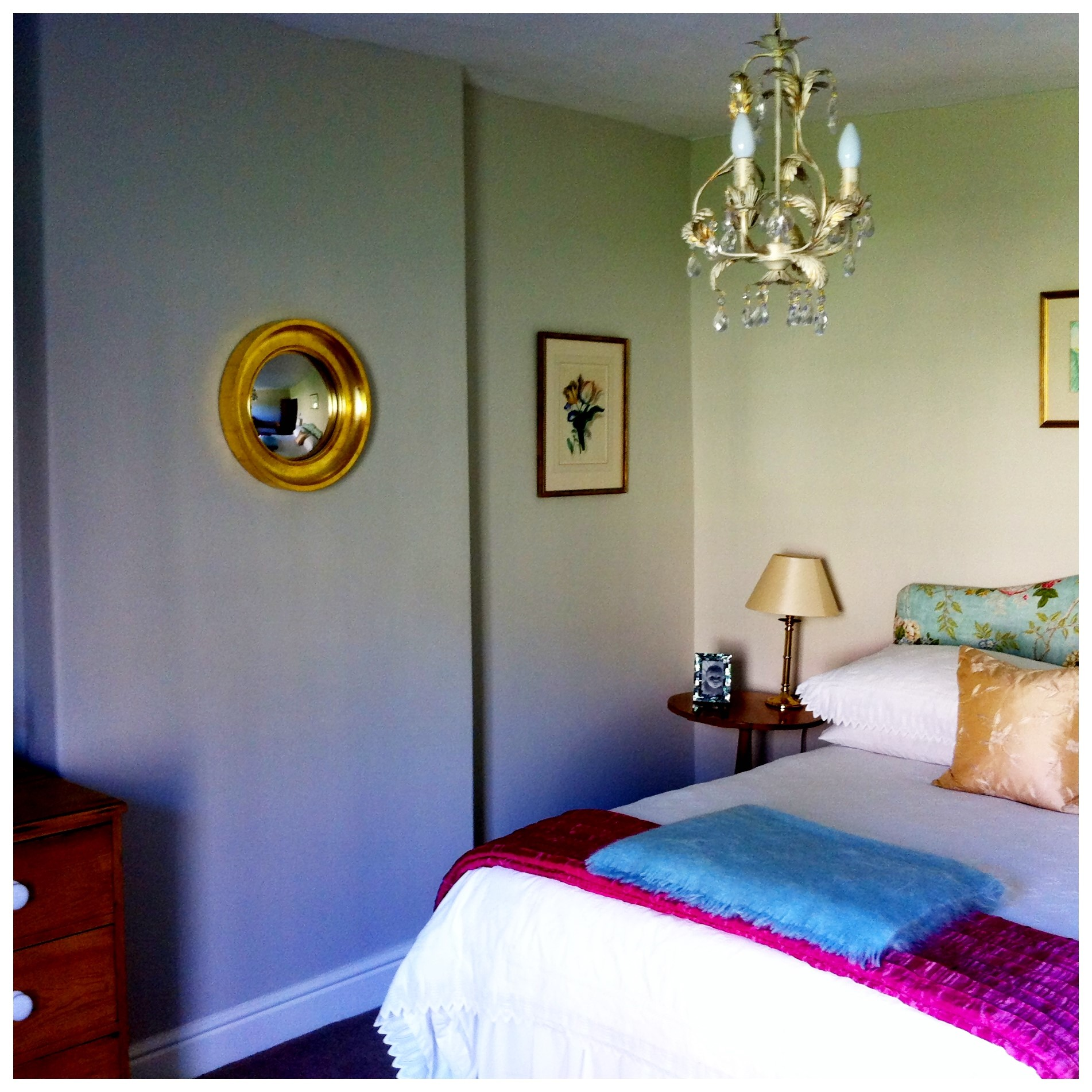 decorative convex mirror with gold frame hanging in a bedroom image