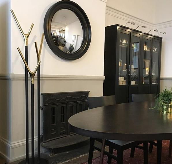 Large black convex mirror over fireplace image