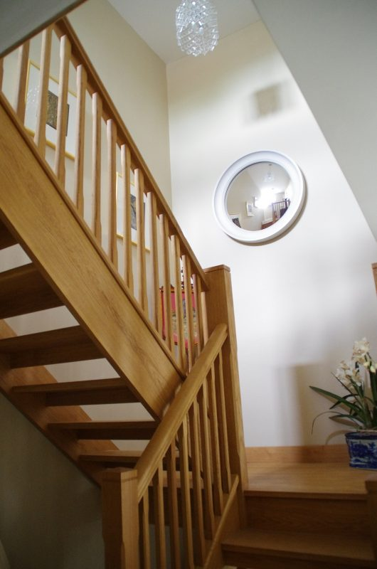 Image of a Large Cavetto convex mirror in palest grey finish hanging in a stairway