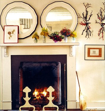 matching round mirrors hanging above a fireplace