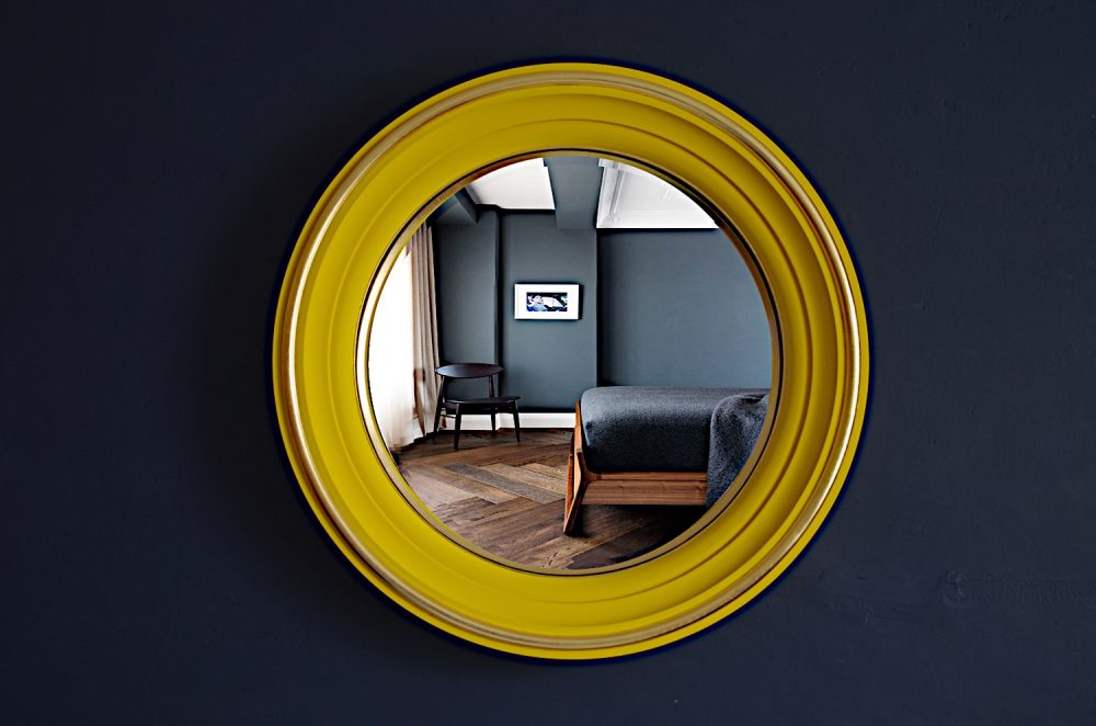 convex mirror with yellow frame hanging on dark blue wall image