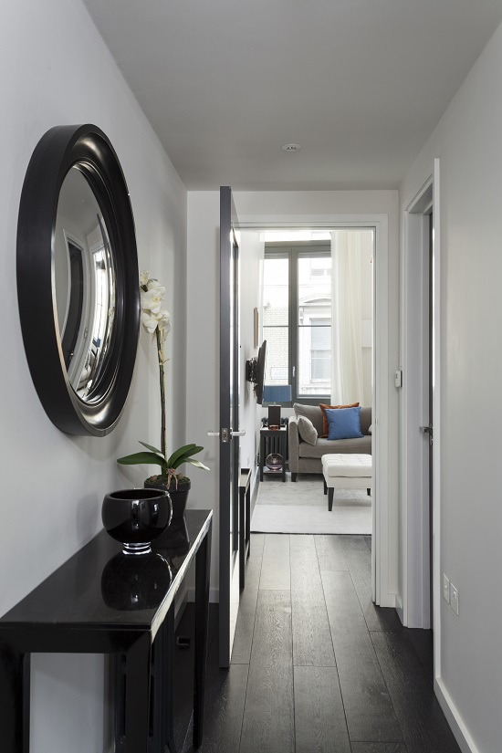 large round mirror with a black frame hanging in a hallway over a console image