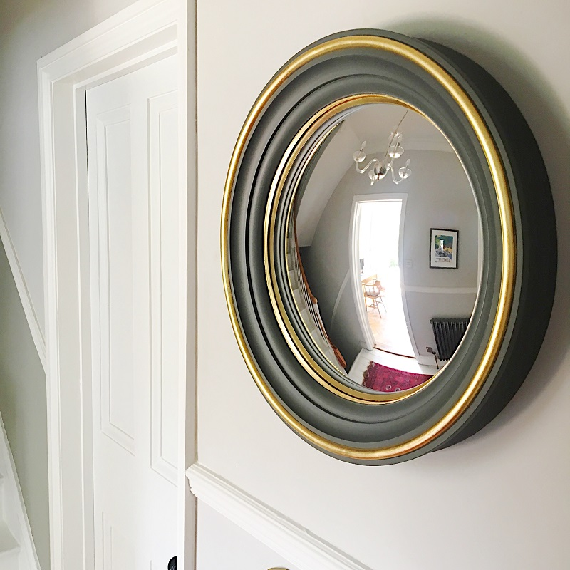 convex mirror with charcoal grey and gilded mirror frame hanging in a hallway image