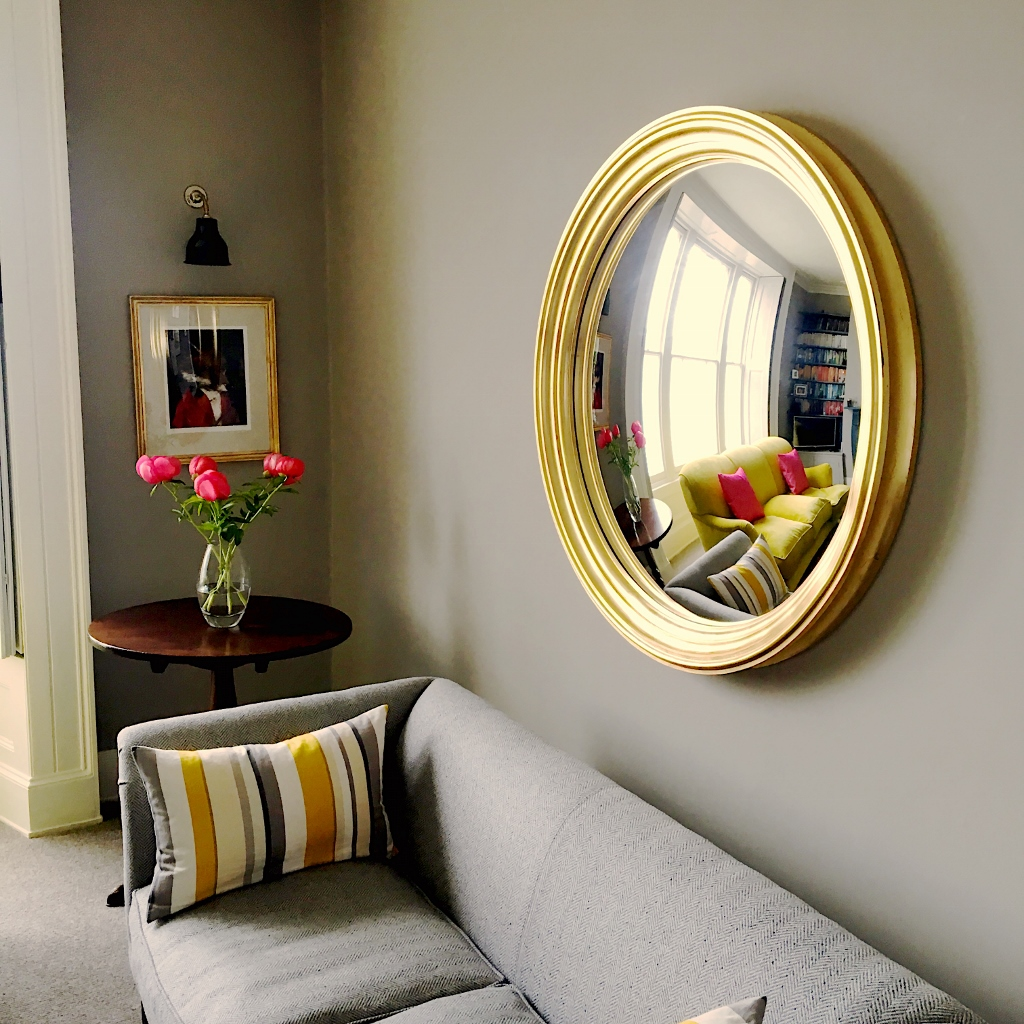 large gold convex mirror hanging above a sofa image