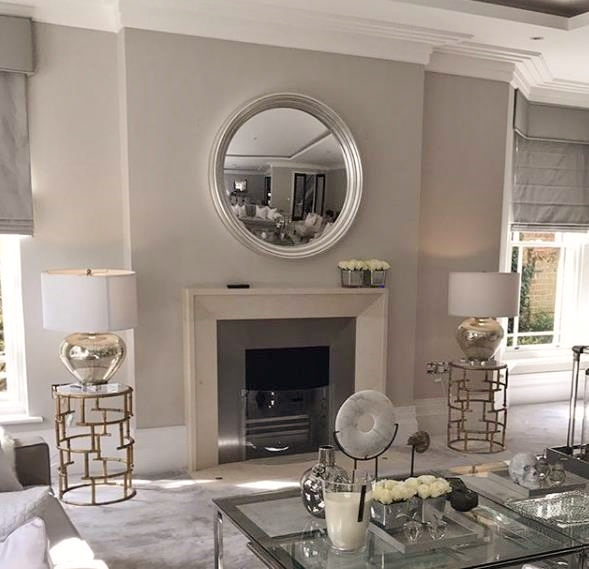 large round convex mirror with silver leaf frame above fireplace image