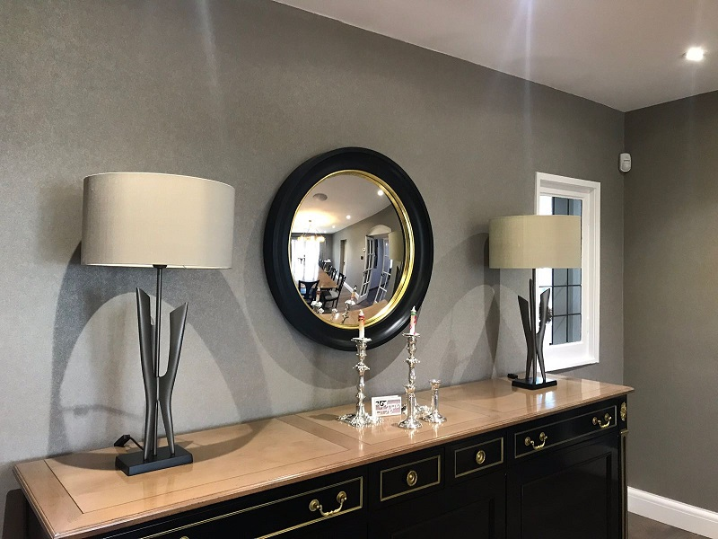 large Black and gold modern convex mirror hanging above a console image