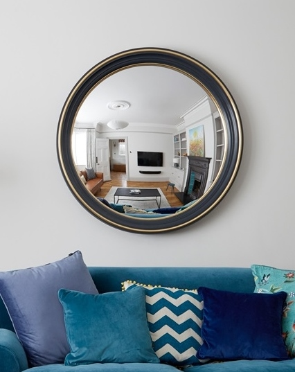 large convex mirror with a dark blue and brass frame hanging above a sofa image